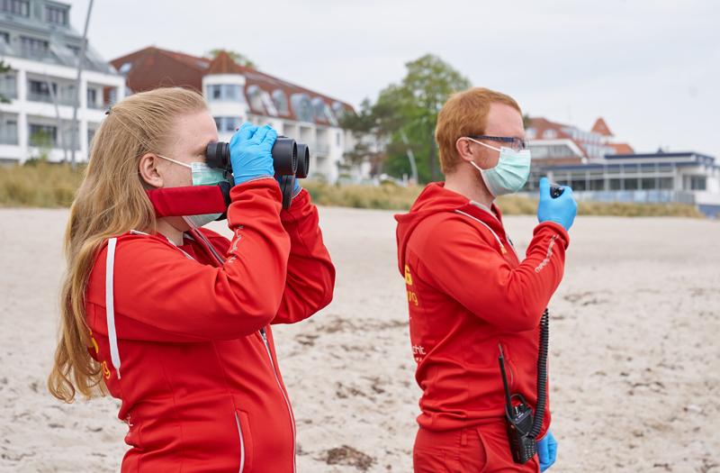 Zwei DLRG Rettungsschwimmer stehen mit Maske und Handschuhen an der Küste und halten Ausschau